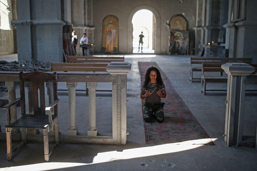 Une femme prie dans la cathédrale du Saint-Sauveur (Ghazanchetsots) endommagée par une attaque à la roquette des forces armées azerbaïdjanaises, le 18 octobre 2020.