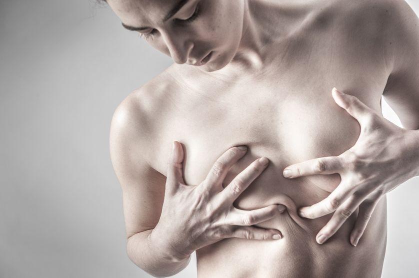 Portrait d'une jeune femme transgenre étouffant sa poitrine