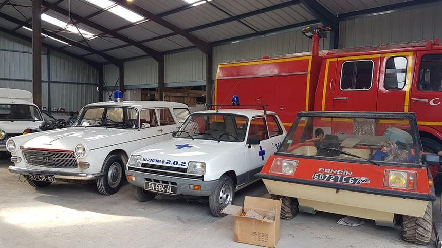 Vielles ambulances et véhicule amphibie dans le hangar de Xavier Hory.
